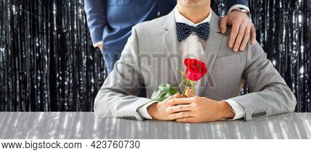 lgbt, homosexuality and same-sex marriage concept - close up of male gay couple with wedding rings and rose flower over foil fringe curtain on background
