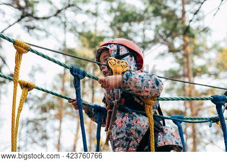 Little Girl 7 Years Old Walk On A Rope Rope Town Bridge In Adventure Rope Park. Childrens Leisure