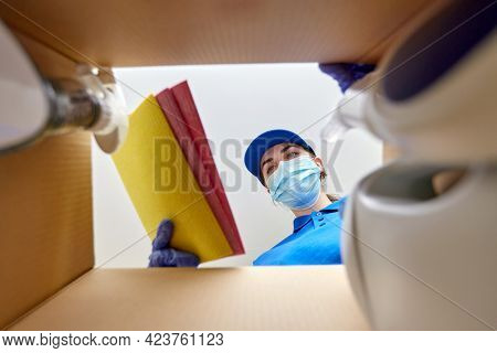 delivery, shipping and pandemic concept - woman in protective medical mask and gloves packing kitchen rags and cleaning supplies to parcel box