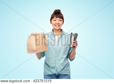 sustainability and people concept - portrait of happy smiling young asian woman in turquoise shirt with thermo cup or tumbler for hot drinks over blue background