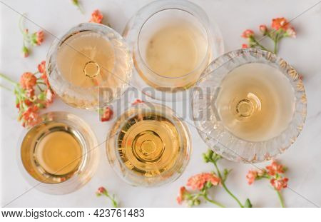 Orange Or Amber Wine And Yellow Flowers Over White Table
