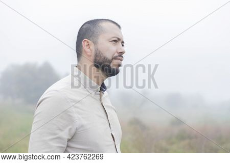 Bearded Latino Man Standing In The Farm On A Cloudy Day