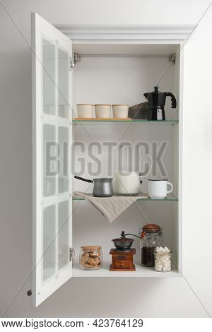 Vintage Coffee Grinder And Other Appliances On Shelving Unit In Kitchen