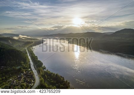 Sunset On The River, Evening Sun Illuminates The Hills And The Road Along The River, Aerial View