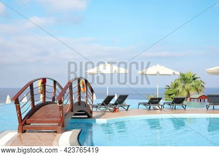 Chaise Longues And Beach Parasols Near Outdoor Swimming Pool At Resort