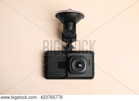 Modern Car Dashboard Camera With Suction Mount On Light Pink Background, Top View