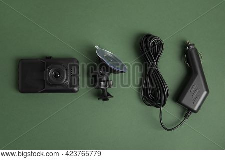 Modern Car Dashboard Camera, Suction Mount And Charger On Dark Green Background, Flat Lay