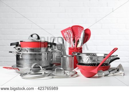 Set Of Clean Kitchenware On White Table Against Brick Wall