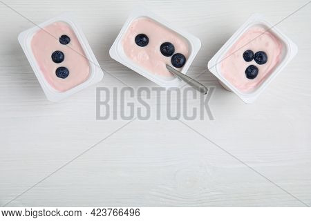 Plastic Cups With Tasty Yogurts And Blueberries On White Wooden Table, Flat Lay. Space For Text