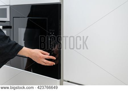 Female Pressing Button On Black Microwave Oven That Attached To Cupboard, Starting Food Cooking Proc