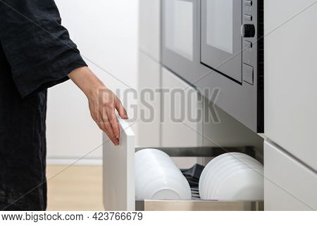 Woman Opening Spacious Storage Drawer That Contains Clean Plates And Dishes, Spacious White Cupboard