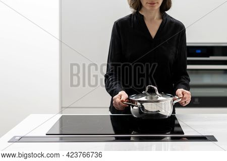 Cropped Shot Of Woman Putting Metal Pot On Glass Induction Stove Built In Kitchen Appliances While C
