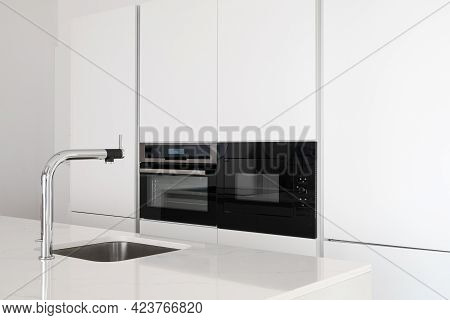 White Glossy Countertop With Shiny Stylish Metal Faucet And Sink In Clean Modern Minimalist Kitchen