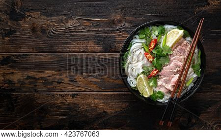Traditional Vietnamese Soup Pho Bo With Beef And Noodles On Wooden Background, Top View, Copy Space