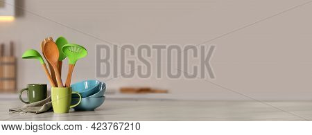 Set Of Different Cooking Utensils And Ceramic Dishes On White Table In Kitchen, Space For Text. Bann