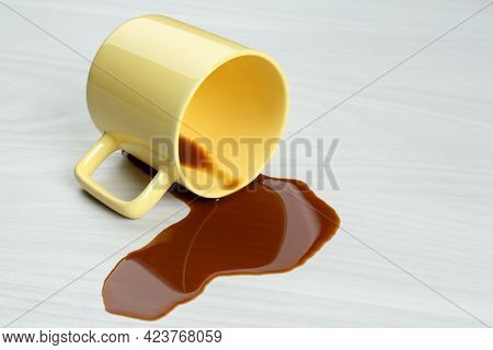 Overturned Cup And Spilled Coffee On White Wooden Table
