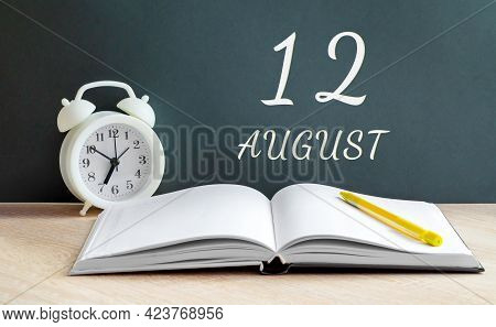 August 12. 12-th Day Of The Month, Calendar Date.a White Alarm Clock, An Open Notebook With Blank Pa