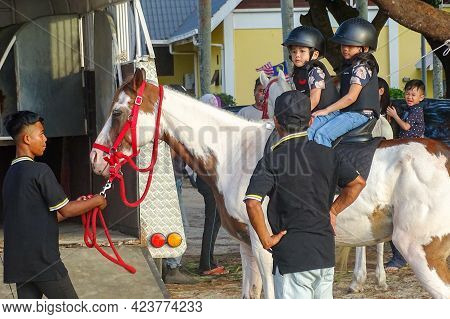 Labuan,malaysia-sept 1,2019:children In Helmet Sitting On Horse And Riding Together Outdoor Park At
