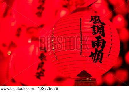 red lanterns hanging up in the night, the Chinese words on lantern means praying
