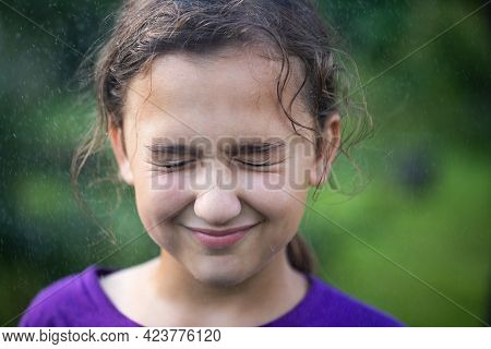 Close-up Portrait Of Child. Happy Cheerful Little Girl With Pronounced Face From Sprayed Small Splas