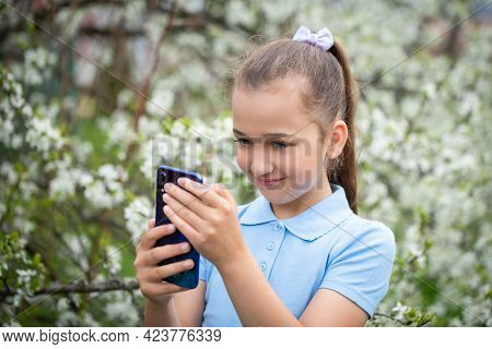 Little Girl Admires New Gadget Smartphone On Background Of Blooming Garden Outdoors In Spring Close-