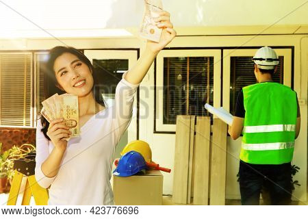 Home Renovation Concept : Pretty Asian Women Enjoy Having The Cash They Have Accumulated To Renovate