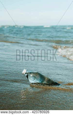 closeup of a glass reusable water bottle on the seashore of a lonely beach, with some blank space on top