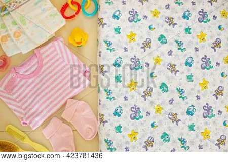 Various Necessary Baby Accessories And Baby Mattress With Pattern On Panel Table Top View.