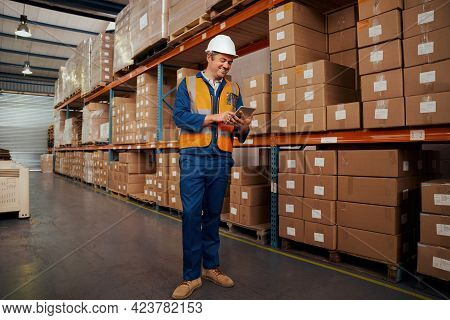 Cheerful Male Warehouse Supervisor Standing In Warehouse Using Smart Tablet