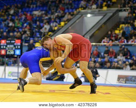 KIEV, UKRAINE - FEBRUARY 16: Match between Mansyrov, Ukraine, blue and Sinitsyn, Ukraine, red, during XIX International freestyle wrestling tournament in Kiev, Ukraine on February 16, 2013