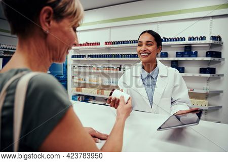 Young Happy Female Pharmacist Wearing Labcoat Giving Bottle Of Medicines To Senior Customer While Ho