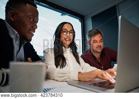 Diverse Colleagues Using A Laptop Together At Work Working On New Business Project