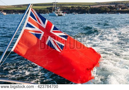 British Red Ensign Flag flying in the wind on the bow or back of a sailing boat, yacht or ship