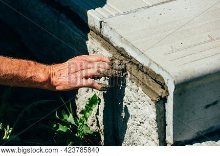 An Old Bricklayer Lays Out Concrete Tiles Outside On A Summer Day. Male Hand With Cement Mortar Clos