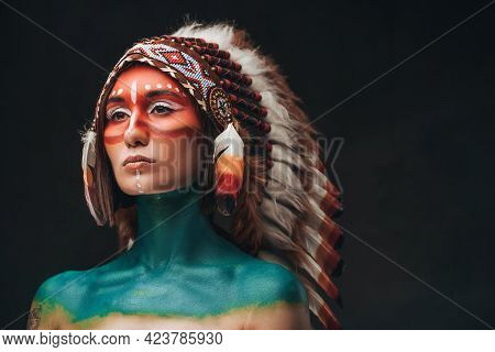 Woman Chief With Indian Headwear Against Dark Background