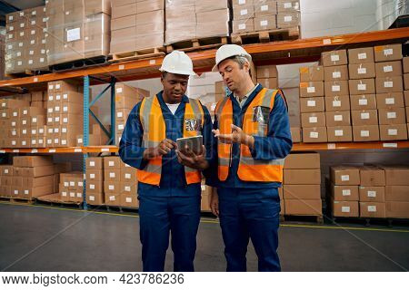 Male Supervisor Gesturing Something While Discussing With His Colleague Using Digital Tablet At Fact