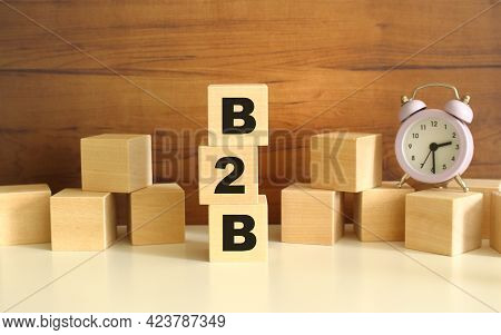 Three Wooden Cubes Stacked Vertically On A Brown Background Make Up The Word B2b. Cubes Are Scattere