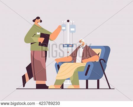 Female Nurse Or Volunteer Checking Dripper Of Elderly Man Patient Home Care Services Healthcare And