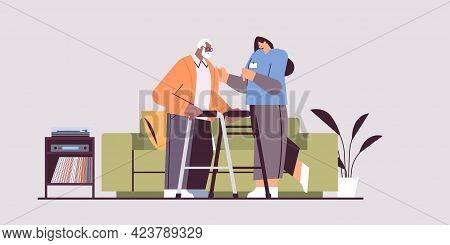 Nurse Or Volunteer Supporting Elderly Man With Walkers Home Care Services Healthcare And Social Supp