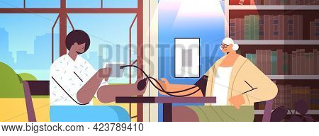 Nurse Or Volunteer Checking Blood Pressure To Elderly Woman Home Care Services Healthcare And Social