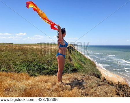 A Woman Standing At The Seashore Looking At Sea Under Blue Sky.