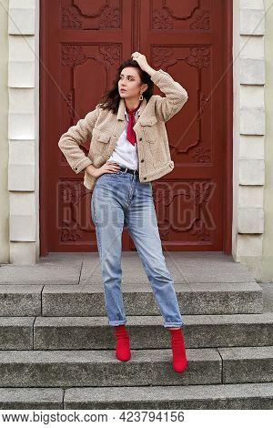 Young Beautiful Woman In Red High Heel Shoes, Blue Denim Jeans Pants And Teddy Jacket Coat Posing On