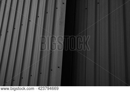 Black Corrugated Iron Sheet Used As A Facade Of A Warehouse Or Factory. Texture Of A Seamless Corrug