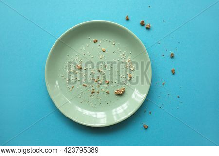 Emty White Plate With Some Crumbs On Light Blue Background. Finished Party And Holidays Concept.
