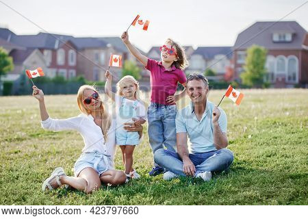 Happy Canada Day. Caucasian Family With Kids Boy And Girl Sitting On Ground Grass In Park And Waving