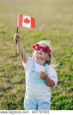 Happy Canada Day. Little Caucasian Toddler Girl In Funny Maple Leaf Sunglasses Waving Canadian Flag.