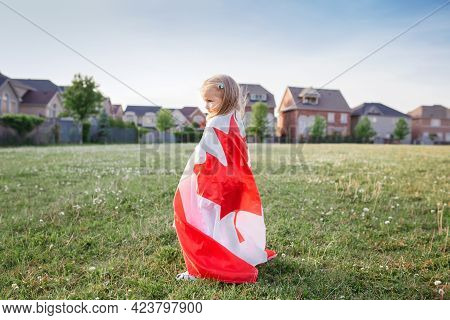 Little Girl Toddler Wrapped In Large Canadian Flag Walking In Park Meadow Outdoor. Canada Day Celebr