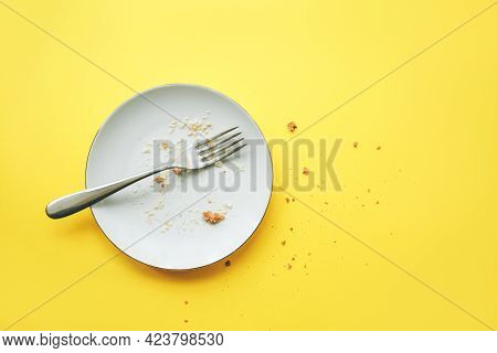 Conceptual Image Of The End Of The Holiday. Empty Round Plate With Crumbs And Fork On It On Yellow B