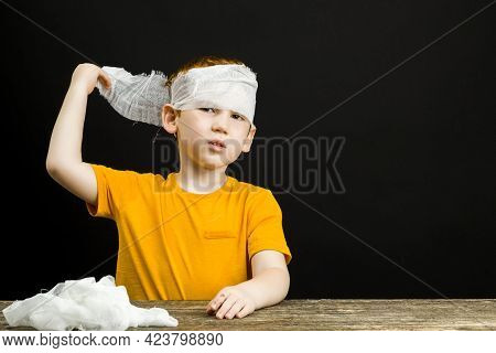 A Beautiful Boy With Red Hair With A Damaged Hand And Fingers Bandages Himself With A Medical Bandag
