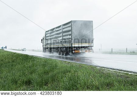 The Movement Of Trucks Of Trucks With A Semi-trailer And Cars On A Wet Road In Rain And Fog And In P